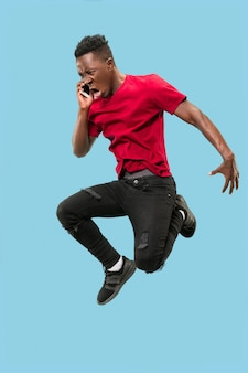 Sempre no celular. comprimento total de um jovem africano bonito pegando o telefone enquanto pula contra o fundo azul do estúdio. mobile, movimento, movimento, conceitos de negócios