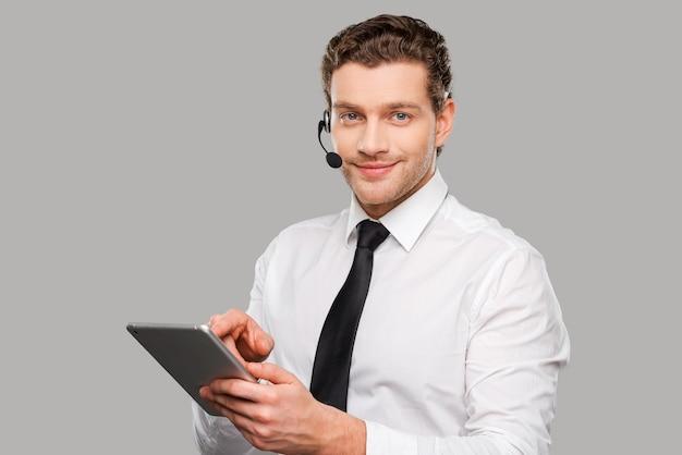Sempre pronto para te ajudar. jovem bonito em trajes formais e fone de ouvido, trabalhando em um tablet digital, em pé contra um fundo cinza