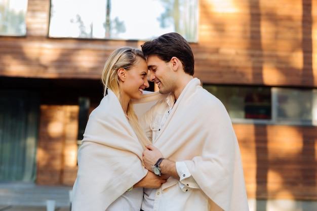 Sendo feliz. casal alegre e positivo olhando um para o outro enquanto usava uma manta