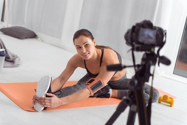 Sendo saudável. jovem blogueira atraente, de cabelos escuros, musculosos, sorrindo e se espreguiçando enquanto está sentada no tapete e fazendo um vídeo para seu blog