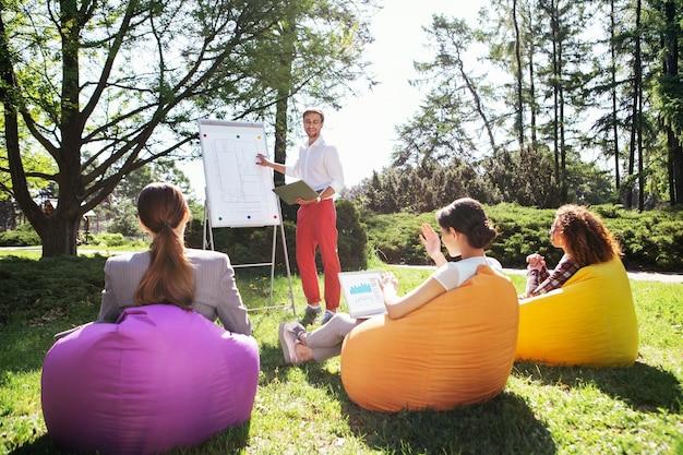 Sendo um estudante. jovem feliz em pé perto do quadro e discutindo o projeto da universidade com os amigos