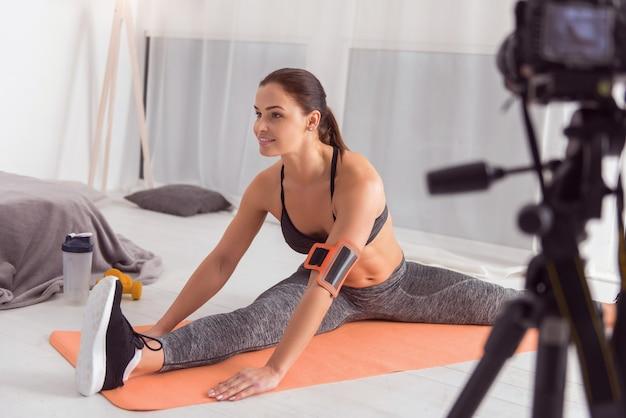 Sendo vigoroso. bela jovem blogueira de cabelos escuros em forma, sorrindo e fazendo esporte enquanto está sentada no tapete e fazendo um vídeo para seu blog