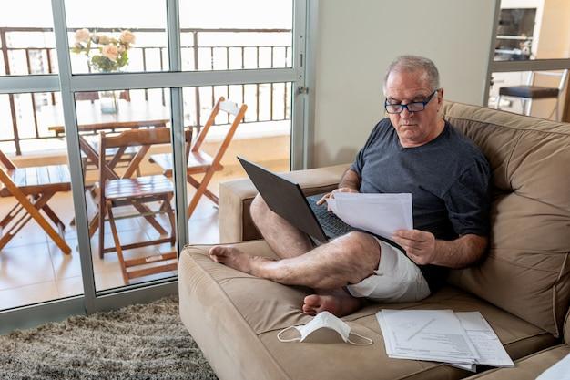 Senhor digitando no notebook, trabalhando em casa no sistema de home office em tempos de pandemia pelo coronavírus. lord trabalha em casa com roupas leves e com a máscara ao lado.