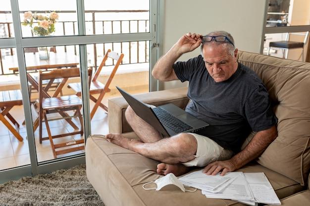Senhor digitando no notebook, trabalhando em casa no sistema de home office em tempos de pandemia pelo vírus covid-19. lord trabalha em casa com roupas leves e a máscara facial ao lado.