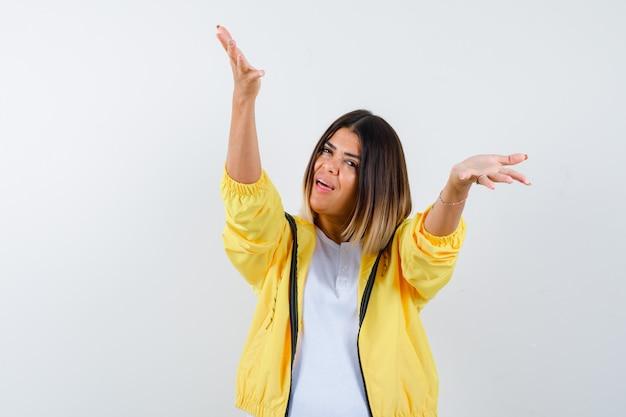 Senhora abrindo os braços para um abraço em camiseta, paletó e parecendo feliz. vista frontal.