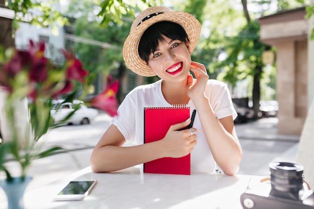 Senhora adorável com expressão facial feliz segurando um caderno vermelho, descansando em um café ao ar livre com o telefone