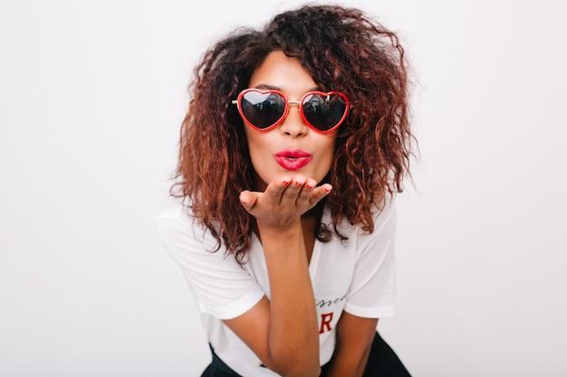 Senhora adorável com pele castanha clara enviando beijo no ar isolado. linda modelo feminino africano com penteado encaracolado, posando em óculos de sol vermelhos da moda.