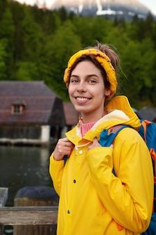Senhora adorável e alegre com sorriso agradável, veste capa de chuva amarela com capuz, carrega mochila