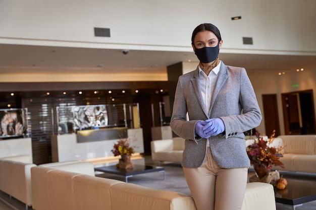 Senhora adulta confiante trabalhando no hotel em máscara de tecido