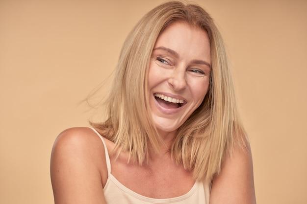 Senhora adulta de camisa olhando para longe e sorrindo no estúdio