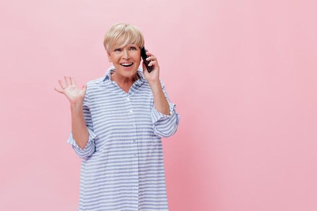 Senhora adulta descolada com uma camisa azul enorme falando ao telefone