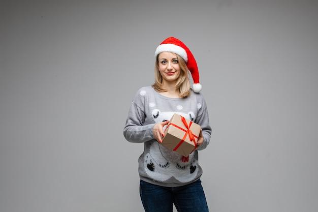 Senhora adulta em jeans e suéter com uma estampa de urso esperando com uma caixa em um papel de embrulho. copie o espaço. conceito de ano novo
