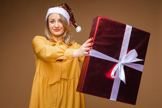 Senhora adulta em um vestido amarelo e chapéu de papai noel com brilhos segurando um presente de natal, embrulhado em um grande pacote. conceito de ano novo