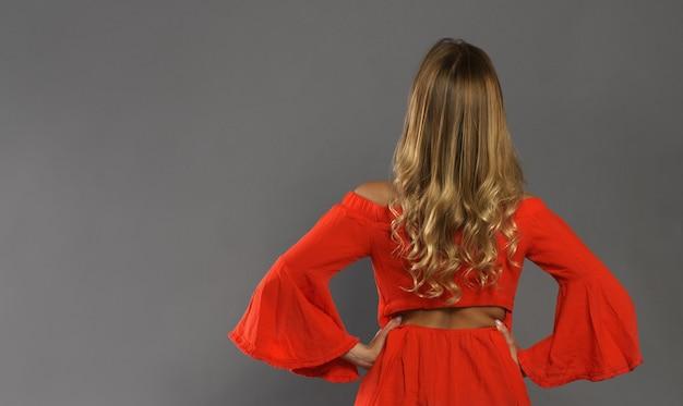 Senhora adulta loira, vestido laranja, olhando para a frente vista traseira