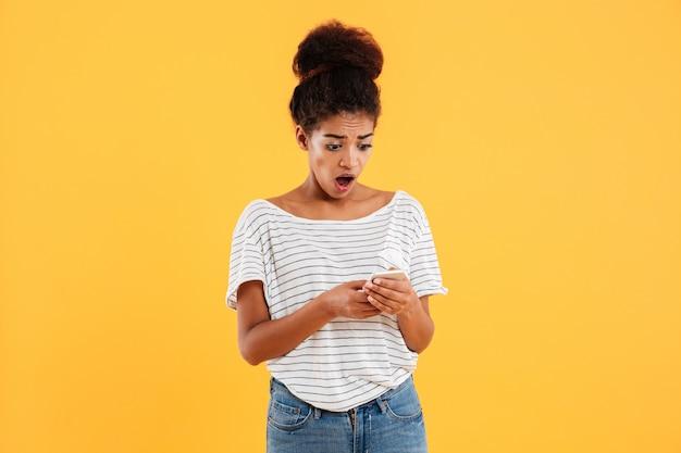 Senhora africana chocada usando e digitando telefone isolado