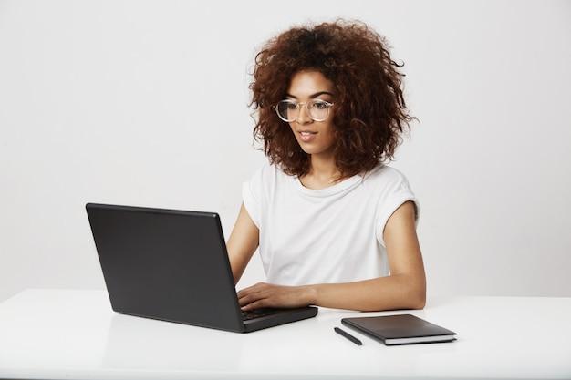 Senhora africana do negócio que sorri trabalhando no portátil sobre a parede branca.