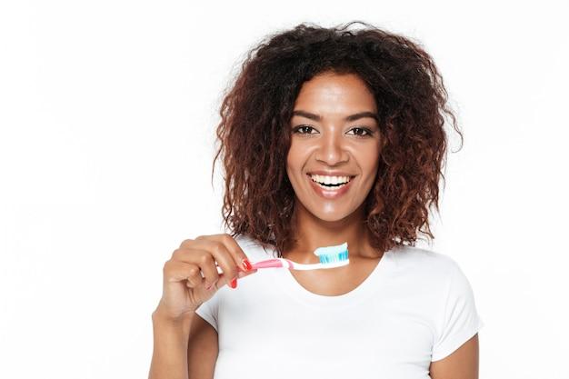 Senhora africana segurando a escova de dentes com creme dental.