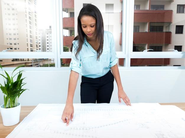Senhora afro-americana, apontando para o plano na mesa