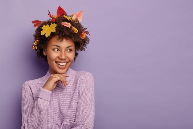 Senhora afro-americana positiva com folhas de outono no cabelo encaracolado e frutos maduros, usa um suéter roxo de malha, focado à parte, isolado sobre a parede violeta, copie a área
