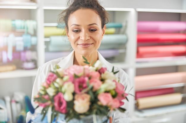 Senhora alegre admirando um ramo de flores rosadas e brancas