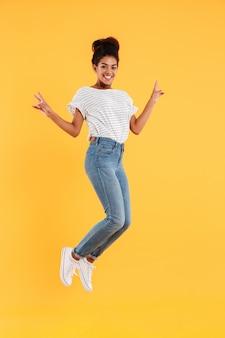 Senhora alegre africana engraçada pulando e sorrindo isolado