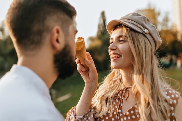 Senhora alegre com chapéu elegante e top de bolinhas ri, borrando o nariz do marido com sorvete de melão.