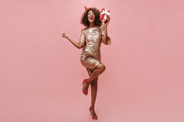 Senhora alegre com penteado encaracolado em um vestido bege brilhante, sapatos legais e boné de férias, regozijando-se e segurando uma caixa de presente vermelha na parede rosa.