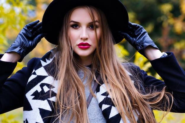 Senhora alegre de chapéu preto e luvas brincando com cabelo comprido com floresta no fundo. linda garota vestindo casaco e lenço elegante, sorrindo durante um passeio no parque outono.