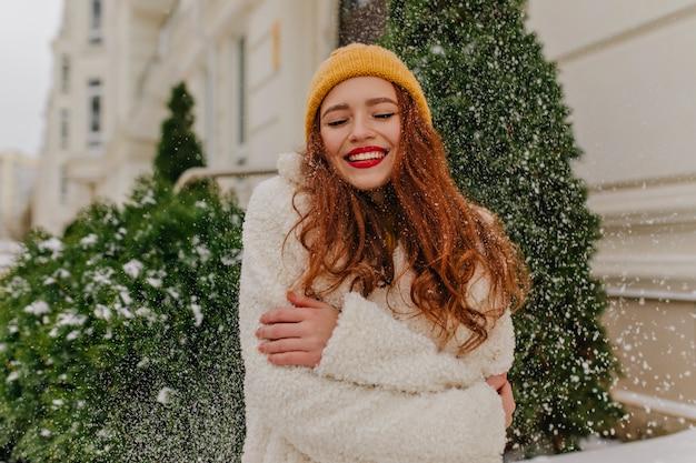 Senhora alegre de gengibre posando sob a neve. mulher adorável sorridente com chapéu de malha em pé perto de abeto.