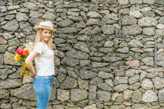 Senhora alegre no chapéu com buquê de flores de volta perto da parede