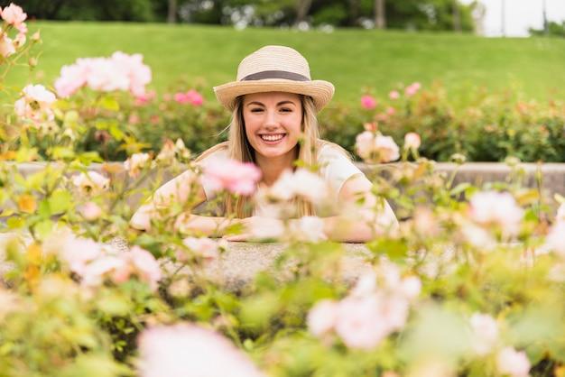 Senhora alegre no chapéu perto de flores brancas no parque