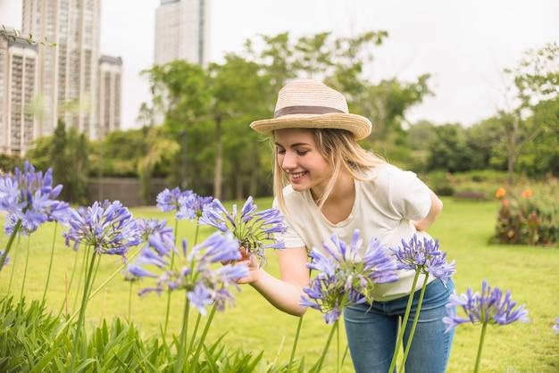 Senhora alegre no chapéu segurando flores azuis no parque da cidade