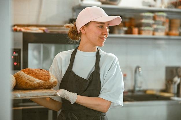 Senhora alegre segurando a bandeja com pão em pé na oficina de padaria artesanal