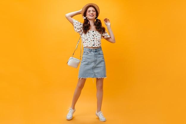 Senhora alegre vestida com saia jeans e top recortado posando com bolsa branca em fundo laranja.