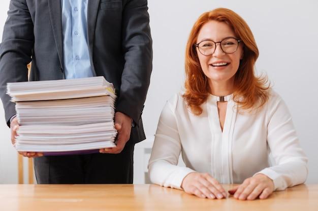 Senhora ambiciosa amigável e responsável sentada em seu local de trabalho e recebendo uma pilha de papéis