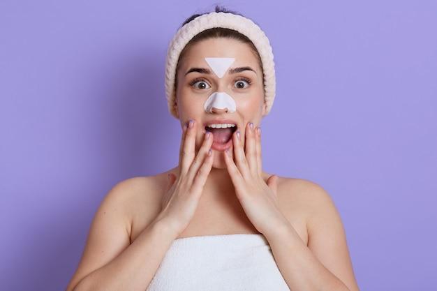 Senhora animada posando com adesivos de pele branca no nariz e na testa, isolada sobre uma parede lilás, fazendo procedimentos de limpeza, mantendo a boca aberta, tocando o rosto, ficando surpresa e maravilhada.