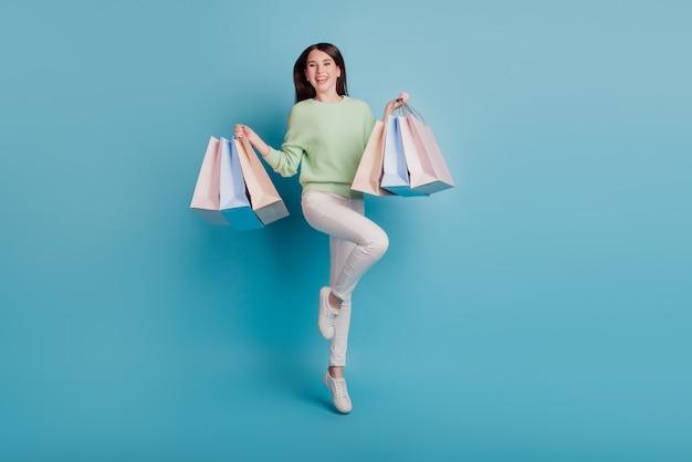 Senhora animada pula e carrega sacolas de compras isoladas em um fundo azul