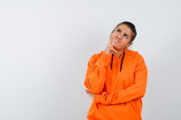 Senhora apoiando o queixo na mão com um capuz laranja e parecendo pensativa