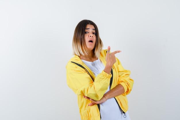 Senhora apontando bem em camiseta, jaqueta e parecendo surpresa. vista frontal.