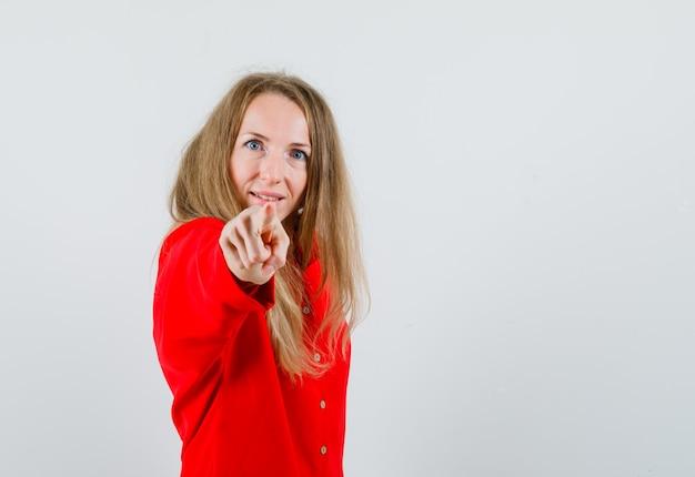 Senhora apontando para a câmera de camisa vermelha e parecendo confiante,