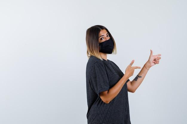 Senhora apontando para a direita em vestido preto, máscara médica e parecendo confiante. vista frontal.