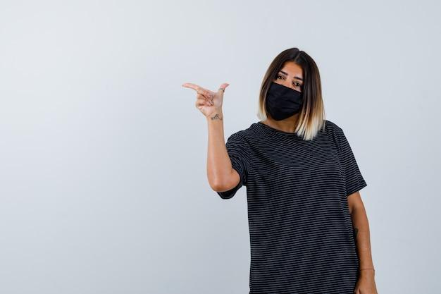 Senhora apontando para a esquerda em um vestido preto, máscara médica e parecendo confiante. vista frontal.
