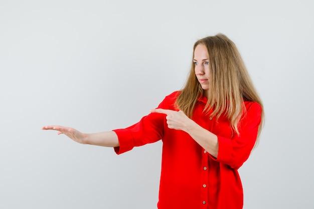 Senhora apontando para algo que fingia estar segurando uma camisa vermelha e parecendo focada,