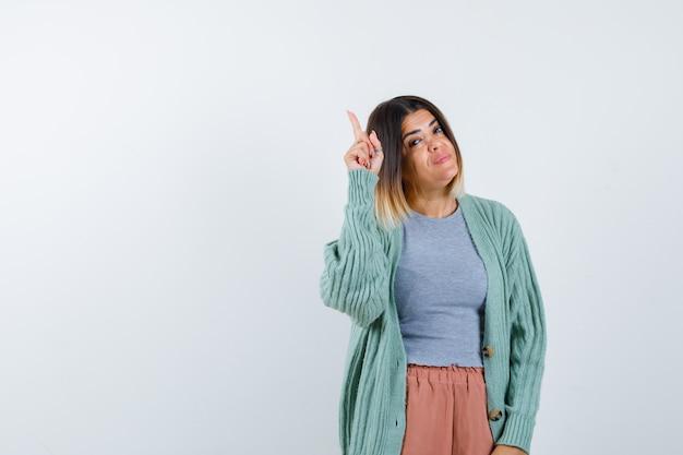 Senhora apontando para cima em roupas casuais e orgulhosa, vista frontal Foto gratuita
