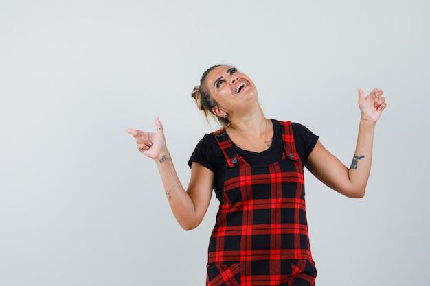 Senhora apontando para cima em um vestido avental e parecendo feliz, vista frontal.