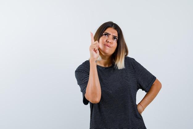 Senhora apontando para cima em uma camiseta preta e parecendo indecisa. vista frontal.