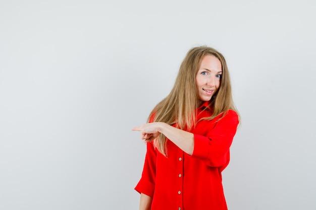 Senhora apontando para longe em camisa vermelha e parecendo alegre.