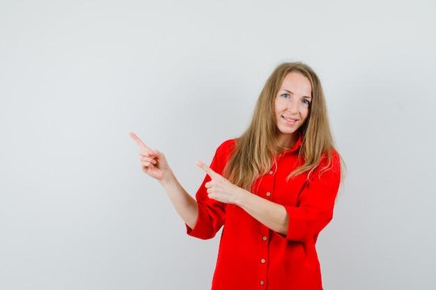 Senhora apontando para o canto superior esquerdo de camisa vermelha e parecendo alegre,