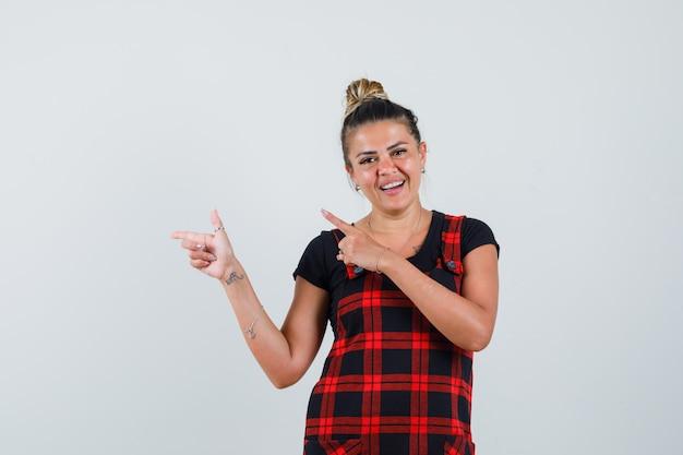 Senhora apontando para o canto superior esquerdo em um vestido avental e parecendo alegre. vista frontal.