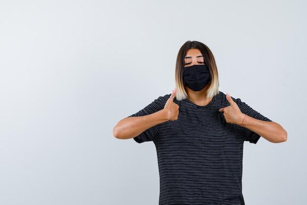 Senhora apontando para si mesma em um vestido preto, máscara médica e parecendo orgulhosa. vista frontal.